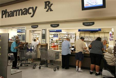 Customers stand in line to pick-up prescriptions at a Wal-Mart in Leesburg, Florida October 6, 2006. REUTERS/Charles W Luzier