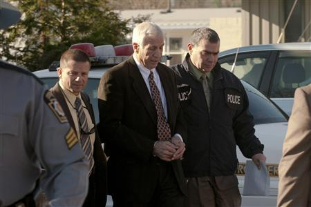 Former Penn State University assistant football coach Jerry Sandusky (C) is led away by police after being arrested in a sex crimes investigation, in Harrisburg, Pennsylvania in this file handout photograph taken November 5, 2011 and released on November 10.  REUTERS/Pennsylvania State Attorney General's Office/Handout