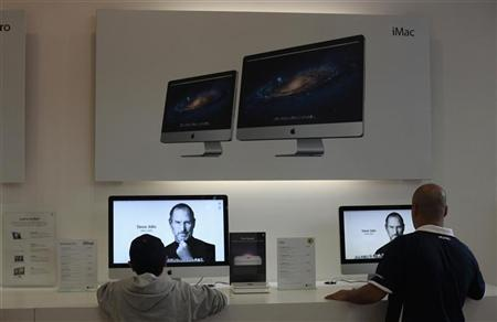 Two people look at the image of Steve Jobs on Apple computers inside the iShop in Guatemala City, October 6, 2011.  REUTERS/Jorge Dan Lopez