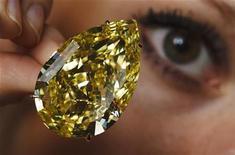 """Модель демонстирует желтый бриллиант """"Капля солнца"""" на пресс-показе в Женеве, 9 ноября 2011 г. Огромный желтый бриллиант, известный под названием """"Капля солнца"""", был продан на аукционе за рекордные $12,36 миллиона во вторник, сообщил аукционный дом Sotheby's. REUTERS/Michael Buholzer"""