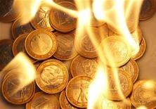 Несколько монет по 1 евро сфотографированы в языках пламени в Вене, 19 июля 2011 года.  Евро обновил минимум месяца в среду утром против доллара и иены, так как долговой кризис еврозоны все сильнее угрожает одной из ключевых стран блока - Франции, чьи долговые бумаги попали под сильное давление. REUTERS/Lisi Niesner