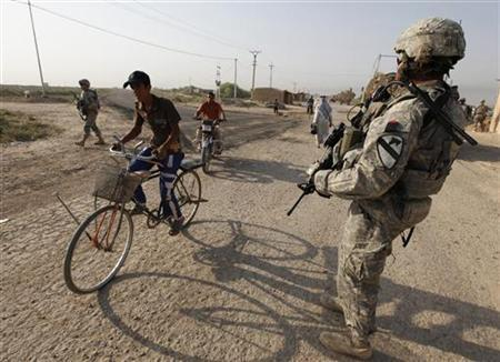 A resident rides a bicycle past U.S. Army soldiers on the outskirts of Kut, southeast of Baghdad, September 21, 2011.    REUTERS/Mohammed Ameen