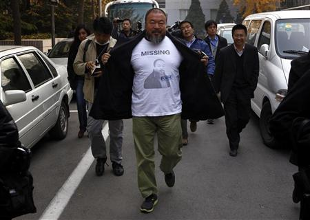 Dissident Chinese artist Ai Weiwei opens his coat to reveal a shirt bearing his portrait as he walks into the government tax office in Beijing November 16, 2011. REUTERS/David Gray