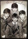 Фотография группы Beatles с автографами участников на выставке в Буэнос-Айресе 4 октября 2010 года. Письмо, написанное Полом Маккартни 12 августа 1960 года, в котором он приглашает барабанщика на прослушивание для группы Beatles, продано за 34.850 фунтов стерлингов ($55.000) на аукционе Christie's. REUTERS/Enrique Marcarian