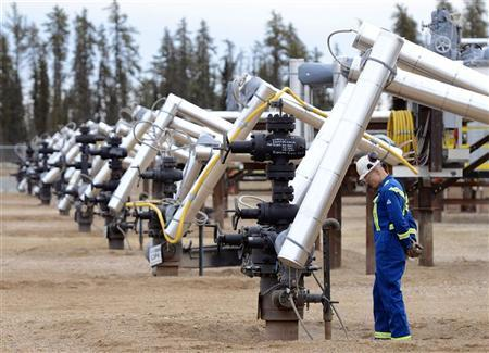 A Statoil oil field worker looks at oil well heads on a well pad at the Statoil oil sands operation near Conklin, Alberta, November 3, 2011.  Statoil plans an expansion of their oil sands operation that will let them produce 60,000 barrels of oil per day by 2016. REUTERS/Todd Korol