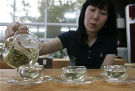 A woman pours hot water to make green tea at a traditional tea house in Boseong, about 397 km (246 miles) south of Seoul, September 23, 2007, which is a famous place in Korea for its extensive and beautiful green tea fields, and has the nation's largest tea outputs.  REUTERS/Han Jae-Ho