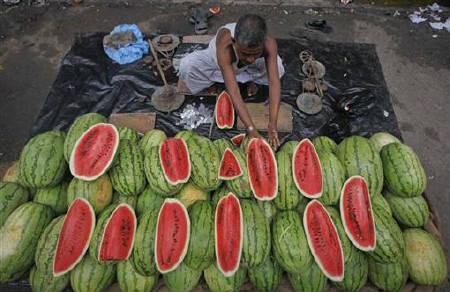 A vendor arranges watermelons for sale along the side of a road in Kolkata August 4, 2011. REUTERS/Rupak De Chowdhuri/Files