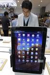Мужчина смотрит планшеты Samsung Galaxy Tab 10.1 в магазине в Сеуле, 28 октября 2011 года. Samsung Electronics начнет производство новой версии своего 10,1-дюймового планшетного компьютера Galaxy уже на этой неделе, чтобы избежать запрета на продажи, наложенного немецким судом. REUTERS/Jo Yong-Hak