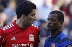 """Форвард """"Ливерпуля"""" Луис Суарес (слева) смотрит на игрока """"Манчестер Юнайтед"""" Патриса Эвра во время поединка в Ливерпуле, 15 октября 2011 года. Футбольная ассоциация Англии (FA) обвинила уругвайского форварда """"Ливерпуля"""" Луиса Суареса в расистских высказываниях, говорится на сайте FA. REUTERS/Phil Noble"""