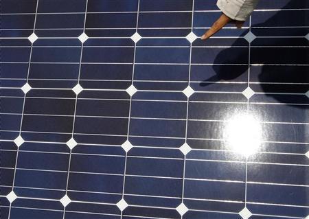 A worker checks solar panels at a solar power field in Kawasaki, near Tokyo July 6, 2011.  REUTERS/Toru Hanai