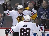 """Хоккеисты """"Чикаго"""" Патрик Шарп (слева) и Патрик Кейн празднуют гол в ворота """"Ванкувера"""". Фотография сделана в Ванкувере 16 ноября 2011 года. Лидер регулярного сезона в Национальной хоккейной лиге """"Чикаго"""" одержал в среду четвертую победу кряду, уверенно переиграв на выезде финалиста прошлого сезона - """"Ванкувер"""" 5-1. REUTERS/Andy Clark"""