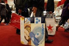 """Люди несут пакеты с покупками, сделанными в """"Черную пятницу"""" в Нью-Йорке, 26 ноября 2010 года. Ажиотаж во время традиционного дня распродаж в США, так называемой """"Черной пятницы"""", в этом году обещает быть еще сильнее, свидетельствуют результаты опроса Национальной федерации ритейла. REUTERS/Jessica Rinaldi"""