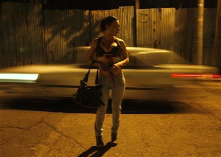 A transgender prostitute waits for clients on a street in Tegucigalpa March 10, 2011.  REUTERS/Edgard Garrido