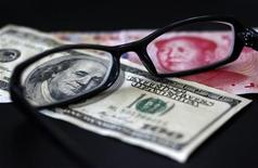 Пара очков лежит на американской и китайской банкнотах. Фотография сделана в Тайбэе 13 октября 2010 года. Экономика Китая набирает обороты, и юань может составить конкуренцию американскому доллару через 5-10 лет, заключила парламентская комиссия США в среду. REUTERS/Nicky Loh