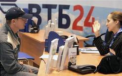 Работница банка ВТБ24 разговаривает с клиентом в московском офисе банка 27 апреля 2007 года. Центральный банк РФ получит право ограничивать максимальные ставки по банковских вкладам физлиц и сможет требовать у кредитных организаций снизить их до уровня не ниже двух третей ставки рефинансирования по депозитам в рублях и не ниже LIBOR - в иностранной валюте, следует из проекта поправок в закон о Центральном Банке России, опубликованном на сайте Минфина. REUTERS/Alexander Natruskin
