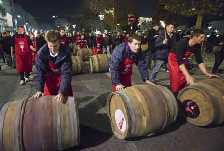 Men roll barrels of Beaujolais Nouveau wine for the official launch of the 2011 vintage in the center of Lyon early November 17, 2011. REUTERS/Robert Pratta