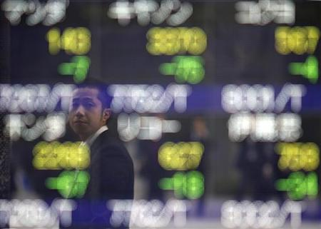 A man is reflected on an electronic board displaying stock prices outside a brokerage in Tokyo November 10, 2011.  REUTERS/Toru Hanai
