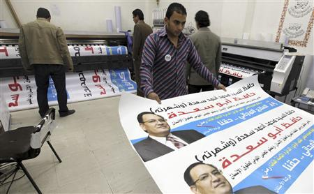 Workers print posters of Hafez Abu Saada, secretary-general of the Egyptian Organization for Human Rights and a political candidate for parliamentary elections, at a workshop in Cairo November 17, 2011. The election follows the removal of President Hosni Mubarak in February after a popular revolt.  REUTERS/Amr Abdallah Dalsh