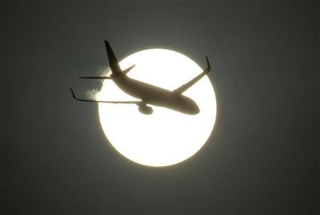 An aircraft is silhouetted by the sun in this file photo. REUTERS/B Mathur