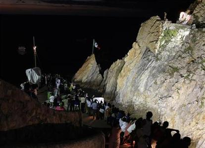 Tourists take photographs of the La Quebrada cliff divers in Acapulco October 21, 2011.   REUTERS/Tomas Bravo