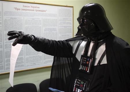 A local resident dressed as the Star Wars Darth Vader shows papers as he visits the mayor's office in Odessa November 14, 2011. An Odessite dressed as the Star Wars villain visited the mayor's office this week to claim a free land plot citing Ukrainian legislation which grants every citizen the right to own 1,000 square metres of land. Picture taken November 14, 2011.  REUTERS/Stringer