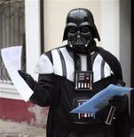 """Человек в костюме Дарта Вейдера демонстрирует документы возле здания мэрии Одессы 14 ноября 2011 года. Человек в костюме Дарта Вейдера, темного героя киносаги """"Звездные войны"""", пришел в мэрию Одессы требовать положенные ему по законодательству 10 соток земли для """"посадки своего корабля"""". REUTERS/Stringer"""