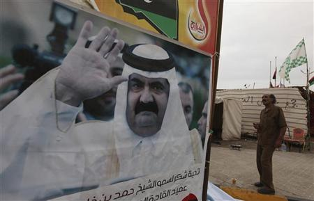 A Libyan man stands next to a poster of Qatar's Emir Sheikh Hamad bin Khalifa al-Thani near the court house in Benghazi June 8, 2011. REUTERS/Mohammed Salem