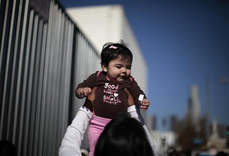 A woman plays with a baby as they wait to go into a ''Back-to-School'' giveaway at the Fred Jordan Mission in Los Angeles, California October 6, 2011.  REUTERS/Lucy Nicholson