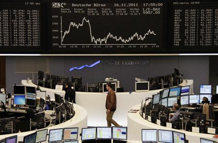 Traders are pictured at their desks in front of the DAX board at the Frankfurt stock exchange, November 16, 2011. REUTERS/Remote/Amanda Andersen