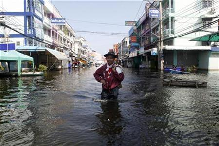 A man carrying his belongings wades through a flooded street in Nonthaburi province, on the outskirts of Bangkok November 18, 2011.  REUTERS/Chaiwat Subprasom