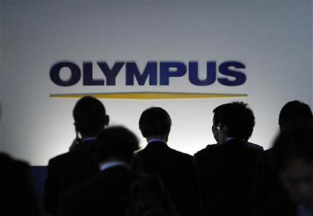 People walk past a sign of Olympus Corp outside the company's showroom in Tokyo November 10, 2011.    REUTERS/Toru Hanai