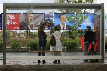 People wait in front of electoral posters of prime ministerial candidate Alfredo Perez Rubalcaba (L) of the Spanish Socialist Workers' Party (Partido Socialista Obrero Espanol) and centre-right People's Party (Partido Popular) leader Mariano Rajoy, at a bus stop in the Andalusian capital of Seville November 19, 2011. REUTERS/Marcelo del Pozo