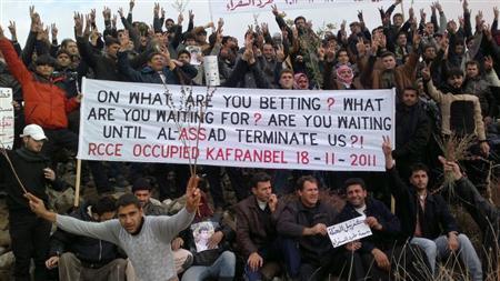 Demonstrators against Syria's President Bashar al-Assad display a banner during a march after Friday prayers in Kafranbel near Adlb November 18, 2011. Picture taken November 18, 2011. REUTERS/Handout