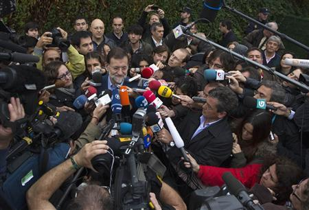 Spain's opposition centre-right People's Party (Partido Popular) leader Mariano Rajoy talks to reporters after casting his vote during a general election in Madrid November 20, 2011. REUTERS/Juan Medina