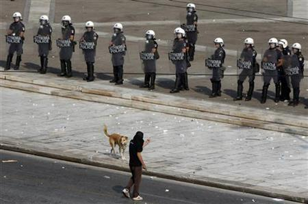 Sausage, a stray dog, is seen between riot policemen and a masked protester during a demonstration in Athens October 5, 2011.  REUTERS/Yannis Behrakis