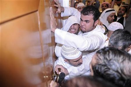 Protesters force open the door of the National Assembly Debate hall during a demonstration in Kuwait City November 16, 2011. Kuwait's emir ordered security forces to take all necessary measures to safeguard ''public order'' after protesters stormed parliament to demand the resignation of the prime minister.  Picture taken November 16, 2011. REUTERS/Stringer
