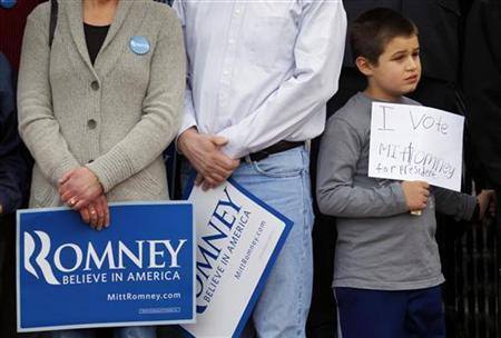 A young supporter holds a handwritten sign for Republican presidential candidate and former Massachusetts Governor Mitt Romney at a campaign rally on the steps of City Hall in Nashua, New Hampshire November 20, 2011.   REUTERS/Brian Snyder