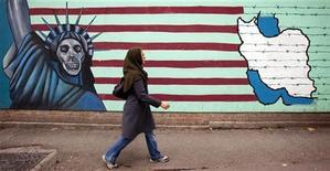 Женщина проходит мимо граффити на стене бывшего американского посольства в Тегеране 19 ноября 2011 года. Иран может использовать нефть как политическое оружие в случае конфликта, связанного с его ядерной программой, заявил министр энергетики Ирана Ростам Каземи в телеинтервью. REUTERS/Raheb Homavandi