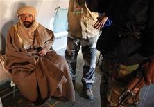 Саиф аль-Ислам сидит в самолете в городе Зинтан, 19 ноября 2011 г. Лояльные Национальному переходному совету Ливии силы задержали бывшего главу разведки режима Муммара Каддафи Абдуллу аль-Сенусси через день после того, как поймали сына Каддафи Саифа аль-Ислама в ливийской пустыне в субботу. REUTERS/Ismail Zetouni