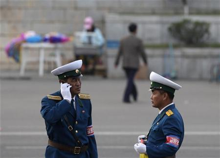 A traffic policeman use a mobile phone in the North Korean capital of Pyongyang October 11, 2010.  REUTERS/Petar Kujundzic
