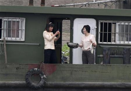 A North Korean woman uses mobile phone to take picture of her compatriot friend on a boat along Yalu River near the North Korean town of Sinuiju, opposite the Chinese border city of Dandong, May 20, 2011.  REUTERS/Jacky Chen