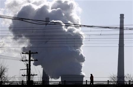 A chimney billows smoke from a coal-burning power station behind powerlines and railway tracks in Beijing December 14, 2010. REUTERS/David Gray