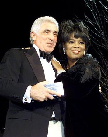 Ted Forstmann, senior partner of the Forstmann Little & Co. investment firm is given a hug by talk show host and editor Oprah Winfrey as she presents him with the Silver Lining Foundation Award, January 23, 2001 in New York City.  REUTERS/Jeff Christensen