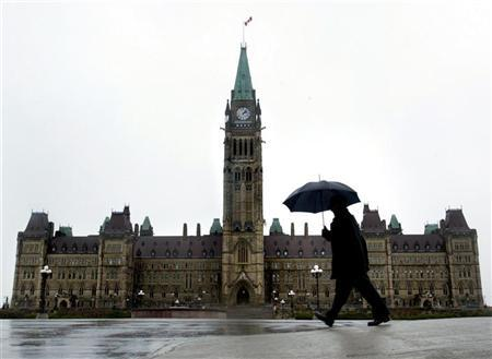 A pedestrian walks in the rain on Parliament Hill in Ottawa, November 13, 2003. REUTERS/Chris Wattie  C
