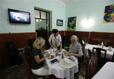 Tourists eat at a ''Paladar'' or home restaurant in the town of Cienfuegos, in central Cuba some 250 kilometres, (155 miles), from Havana January 20, 2011. REUTERS/Desmond Boylan