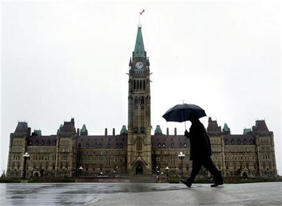 A pedestrian walks in the rain on Parliament Hill in Ottawa, November 13, 2003.  REUTERS/Chris Wattie  CW/HB
