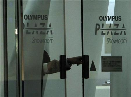 A man closes door of Olympus Corp's showroom in Tokyo November 10, 2011.    REUTERS/Toru Hanai