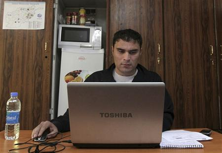 Mohammad Zaher Moshtaq an Afghan employee working for a U.S. company uses his computer at his office in Kabul November 20, 2011. REUTERS/Omar Sobhani