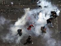 Протестующие пытаются убежать от гранаты со слезоточивым газом на площади Тахрир в Каире 21 ноября 2011 года. Египетские демонстранты призывают своих сторонников выйти на улицы во вторник, чтобы положить конец правлению в североафриканской стране военных, перед которыми встала еще одна дилемма - принимать или нет отставку гражданского правительства. REUTERS/Amr Abdallah Dalsh