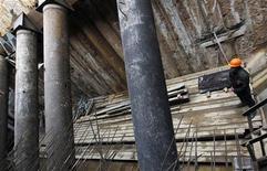 Рабочий стоит около укреплений на стройке станции метро Новокосино в Москве, 12 октября 2011 года. Москва хочет сэкономить десятки миллиардов рублей на строительстве метро, отдав одну из веток в концессию частным инвесторам, сообщил журналистам во вторник глава метрополитена Иван Беседин. REUTERS/Anton Golubev